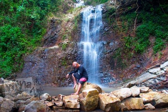 Seorang pria berkepala gundul berbaju hitam merenung di area sungai Grojogan Kali Bulan Bantul saat zaman dulu