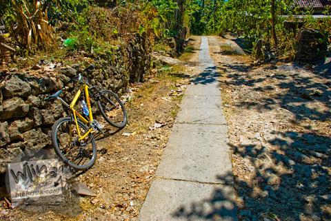 jalan desa setapak dari semen yang mengarah ke Sendang Bayutemumpang di Desa Bangunjiwo, Kasihan, Bantul, Yogyakarta