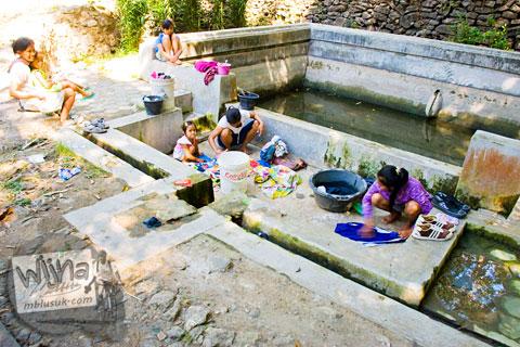 pemandangan suasana ibu-ibu wanita desa sedang mencuci baju sambil mengobrol di Sendang Bayutemumpang yang ada di Desa Bangunjiwo, Kasihan, Bantul, Yogyakarta