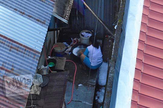 Warga wanita mencuci baju dengan tangan di Belitung di tahun 2016