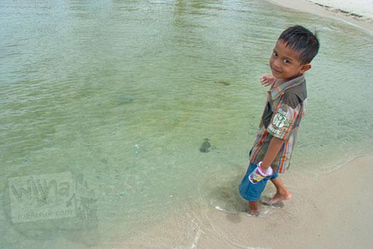 bocah anak kecil cowok Manggar sedang bermain air di Pantai Nyiur Melambai di Belitung Timur pada Maret 2016