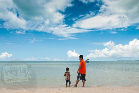 seorang bapak dan anaknya bermain air di Pantai Nyiur Melambai di Belitung Timur pada Maret 2016