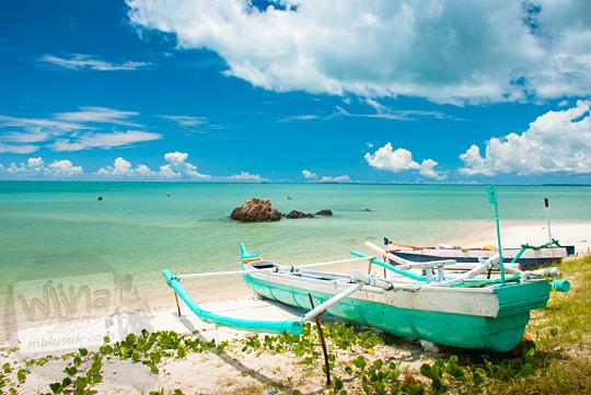 foto indah suatu sudut tersembunyi sepi yang jarang didatang orang di Pantai Nyiur Melambai di Belitung Timur pada Maret 2016 tempat perahu nelayan berlabuh di pantai pasir putih dan langit biru
