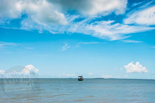 Perahu nelayan mengapung terbawa ombak di Pantai Nyiur Melambai di Belitung Timur pada Maret 2016