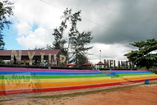 Teks besar bertuliskan nama Pantai Nyiur Melambai di Manggar, Belitung Timur dengan warna-warni pelangi pada Maret 2016