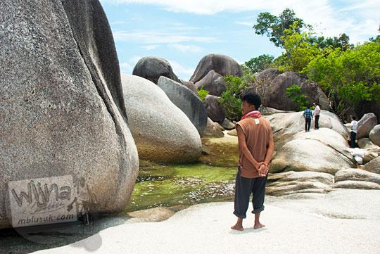 seorang bapak juru pelihara kebersihan Pantai Tanjung Tinggi sedang berjaga mengawasi pengunjung wisatawan berfoto di area batu granit raksasa pada Maret 2016