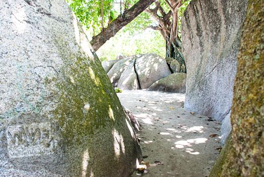 gang celah jalan setapak kecil berpasir di antara dua batu granit besar di kawasan Pantai Tanjung Tinggi pada Maret 2016