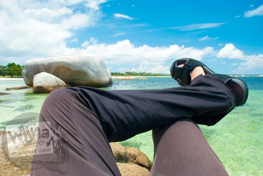 foto wisatawan di Pantai Tanjung Tinggi Belitung merebahkan diri di atas batu granit dengan posisi kaki diangkat menyilang pakai celana panjang pada Maret 2016