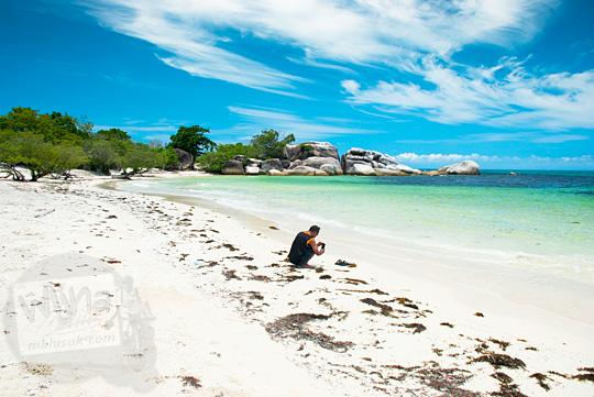 seorang pria laki-laki cowok sedang jongkok sendirian di bibir Pantai pasir putih Tanjung Tinggi Belitung memotret sandalnya pakai kamera handphone pada Maret 2016