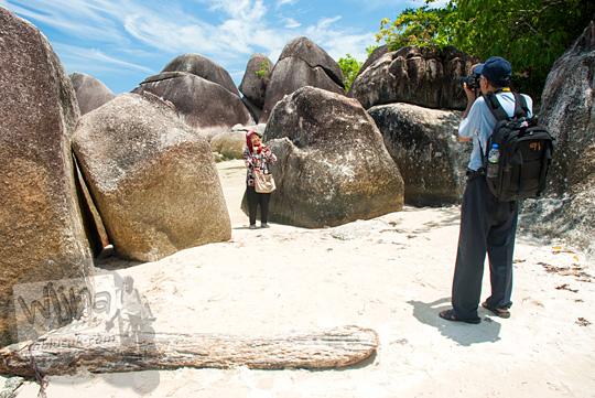 wisatawan wanita berjilbab berfoto dengan fotografer latar batu granit besar di Pantai Tanjung Tinggi pada Maret 2016