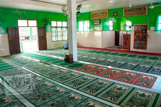 suasana di dalam masjid al huda desa Tanjung Binga Belitung dengan shaf dari karpet merah hijau pada Maret 2016