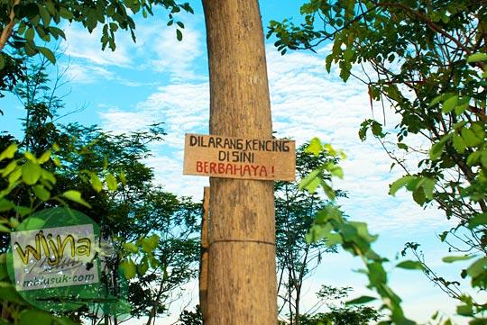 papan larangan mistis berbahaya buang air (kencing) di salah satu pohon di kawasan Bukit Kendil, Borobudur, Magelang