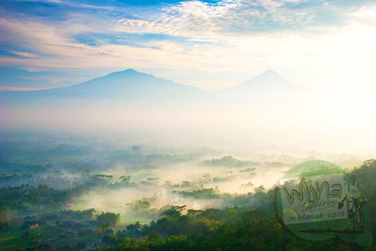 Gunung Merapi dan Gunung Merbabu di pagi hari di tengah pemandangan hamparan kabut dilihat dari Bukit Kendil