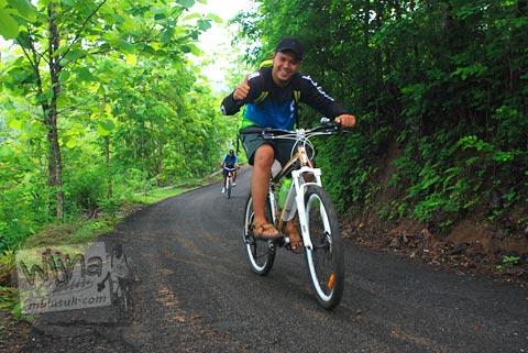 Meindraset, Indra Setiawan bersepeda menuju kawasan Gua Jepang Pundong dan Gua Surocolo di Pundong, Bantul pada Desember 2015