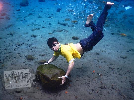Berpose sambil memegang batu yang ada di dasar kolam Umbul Ponggok, Klaten supaya stabil