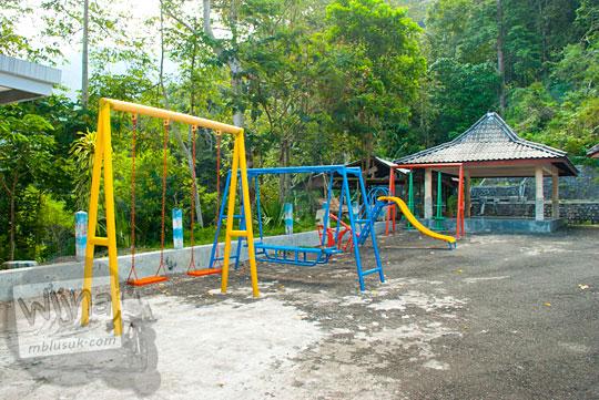 harga membangun kompleks wahana permainan jungkat-jungkit ayunan perosotan anak-anak di kawasan wisata Air Terjun Dolo, Besuki, Kediri dekat mushalla lokasi parkir kendaraan pada September 2016