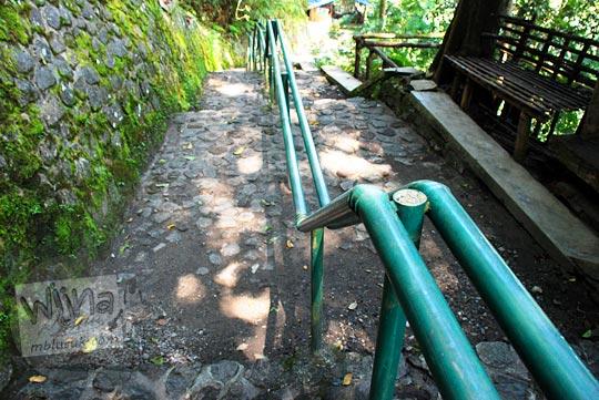 Wujud jalan setapak ratusan tangga dari batu dibatasi besi hijau menuju ke dasar Air Terjun Dolo, Desa Jugo, Mojo, Kediri pada September 2016