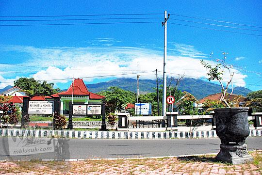 pemandangan di dekat kantor kecamatan plaosan magetan berlatar gunung lawu yang puncaknya tertutup awan