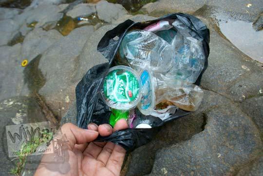 Memunguti sampah yang tercecer di hutan