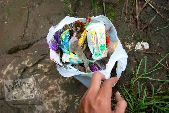 Memunguti sampah yang tercecer di air terjun