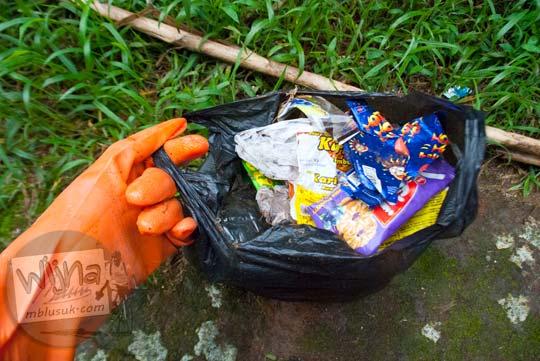 Memunguti sampah yang tercecer di lokasi wisata