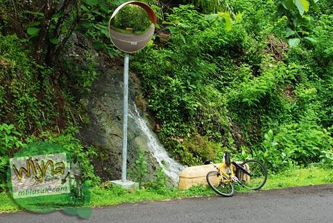 berhenti bersepeda di pinggir jalan raya menikmati air terjun di samigaluh, kulon progo