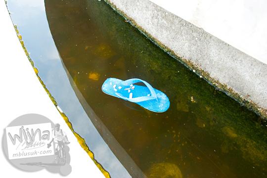 Sampah sandal mengapung di kolam di dasar monumen Perahu Tradisional Riau di kawasan Stadion Utama Riau Pekanbaru