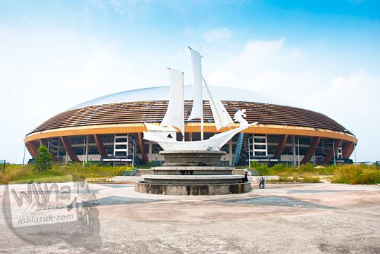 Tampak samping Stadion Utama Riau Pekanbaru dengan latar depan monumen perahu tradisional Riau