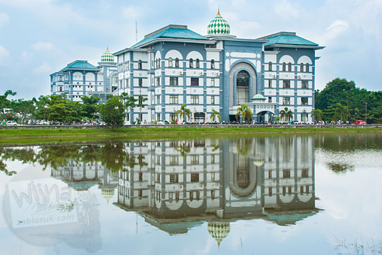 pemandangan gedung perpustakaan pusat terpantul di danau Kampus UIN Sultan Syarif Kasim, Pekanbaru, Riau pada tahun 2016