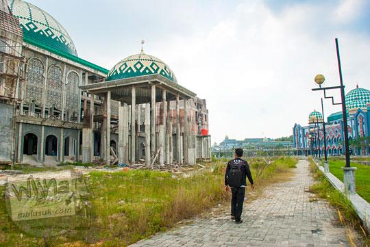 seorang mahasiswa berjalan kaki di dekat masjid Kampus UIN Sultan Syarif Kasim, Pekanbaru, Riau yang belum jadi pada tahun 2016