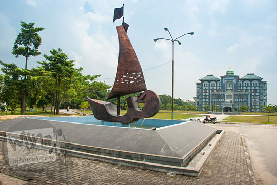 patung perahu jukung tradisional melayu dari perunggu pajangan di depan gedung pusat Kampus UIN Sultan Syarif Kasim, Pekanbaru, Riau pada tahun 2016