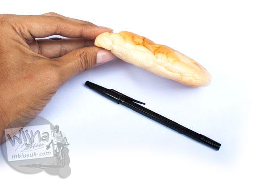 perbandingan ukuran roti cokelat larisa dengan bolpoin pulpen tangan manusia