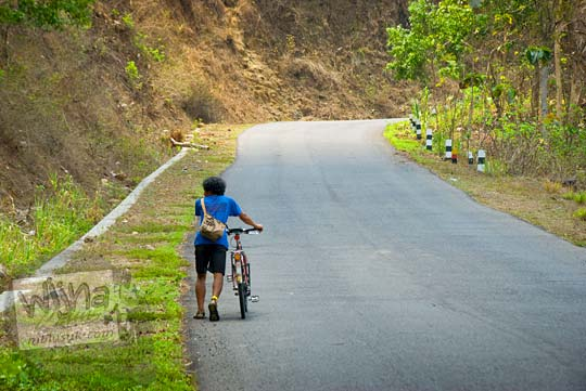 Menuntun sepeda federal melewati Tanjakan arah ke Gua Kiskendo di Girimulyo, Kulon Progo