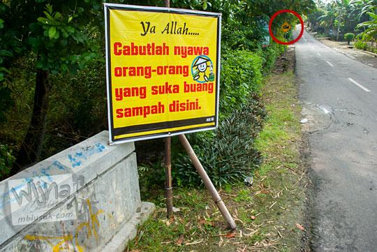 papan ancaman nyawa larangan membuang sampah sembarangan mati Tuhan letaknya dekat perumahan cluster 1 villa chinta ayu di ruas jalan dari Playen ke Karangmojo, Gunungkidul pada April 2016