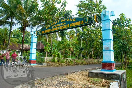 rute angkutan umum lewat gapura masuk ke lokasi ziarah umat kristen katolik Taman Doa Goa Maria Sendang Rosario Ngijoreja yang terletak di tepi jalan dari Playen ke Karangmojo, Gunungkidul pada April 2016
