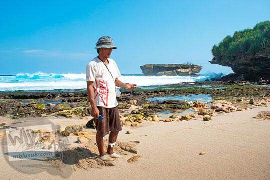 seorang bapak pemancing di pantai Gunungkidul sedang mencari cacing laut untuk umpan dengan latar pulau Timang