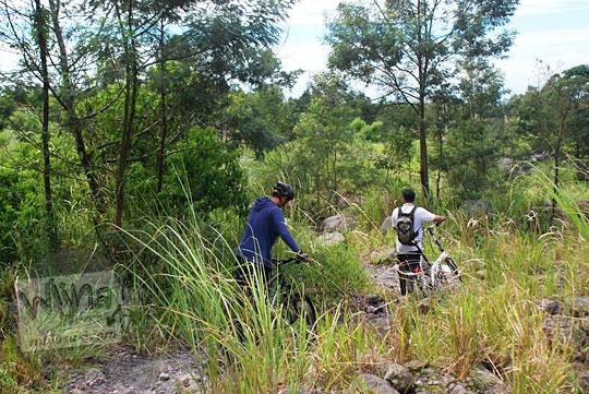 dua orang menuntun sepeda mtb dan sepeda lipat menembus semak belukar di pinggir hutan lereng gunung merapi setelah menyebrang jurang dalam dari desa kinaherjo ke arah obyek wisata kaliadem tempat parkir jeep lava tour pada Februari 2016