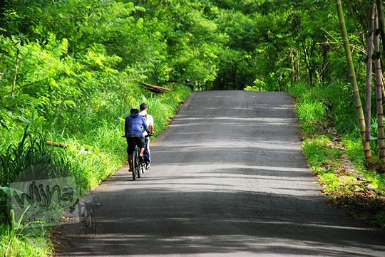 dua pesepeda dengan sepeda lipat dan sepeda mtb sedang menanjak jalan aspal sekeliling hutan yang sepi dari rumah makan moro lejar cangkringan ke arah obyek wisata kali kuning pada Februari 2016
