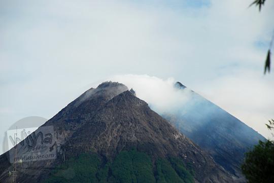 foto puncak gunung merapi yang cerah berawan dengan asap mengepul dipotret dari jalan bebeng arah ke kaliadem pada suatu pagi di bulan Februari 2016