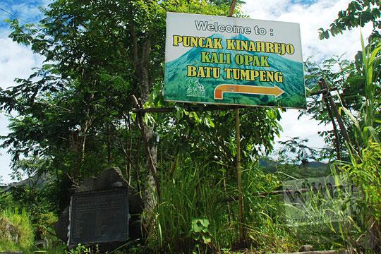 papan petunjuk ke arah obyek menarik puncak kinahrejo, kali opak, serta batu tumpeng terletak di cabang jalan desa kinaherjo terkena dampak erupsi merapi tahun 2010