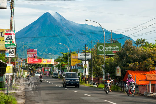 pemandangan jalan raya kaliurang sekitar kilometer 14 setelah kampus universitas islam indonesia (uii) pada pagi hari bulan Februari 2016 yang cerah dengan latar gunung merapi tampak jelas anggun dari kejauhan