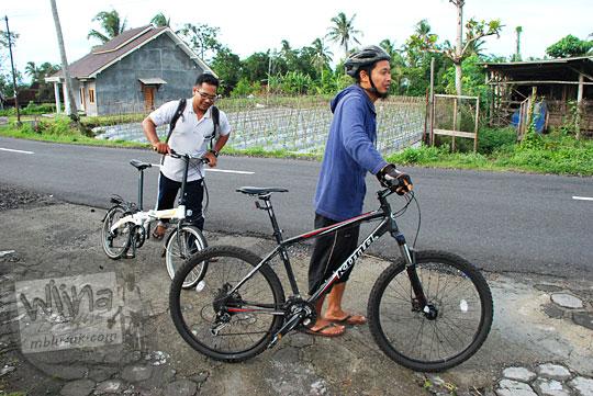 dua orang pesepeda pria satu naik sepeda lipat dan yang satu naik sepeda mtb sedang berusaha menyeberang jalan raya pakem cangkringan prambanan dari depan rumah makan moro lejar pada suatu pagi di bulan Februari 2016