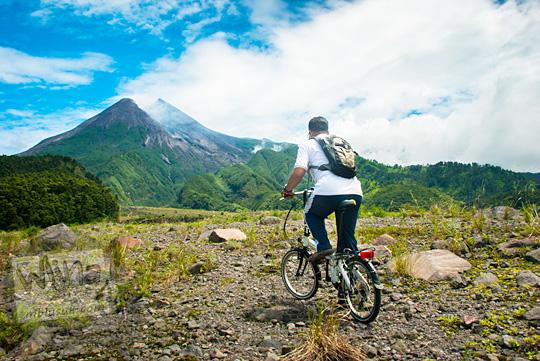 seorang pria naik sepeda lipat bersepeda di obyek wisata kaliadem cangkringan yogyakarta menuju ke arah gunung merapi terlihat cerah besar difoto dari belakang pada Februari 2016