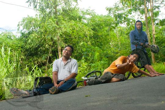 pesepeda yogyakarta yang bersepeda dari jogja cangkringan ke kaliadem beristirahat sambil berfoto selfie di tengah jalan aspal menanjak yang miring dengan ceria