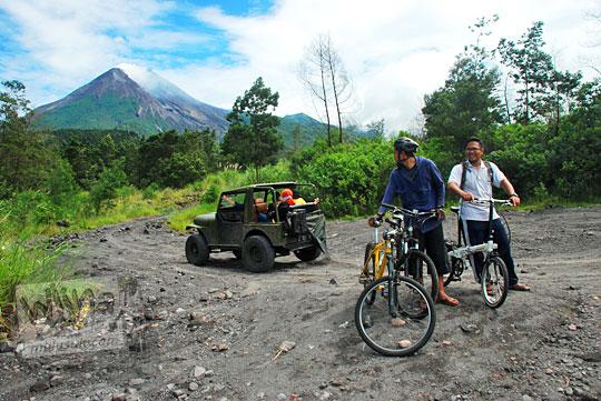 dua orang naik sepeda mtb dan sepeda lipat dari cangkringan ke kaliadem berjumpa dengan operator jasa jeep lava tour merapi menawarkan paket wisata harga murah khusus untuk pesepeda arah kaliurang pada Februari 2016