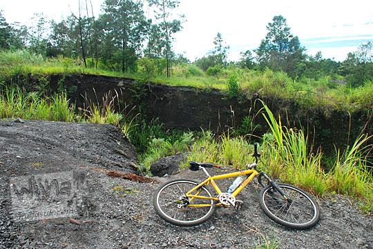sepeda mtb kuning tergeletak di pinggir jurang besar dalam menganga yang menghubungkan desa kinahrejo dan kaliadem kondisi jalannya rusak putus terkena lahar dingin merapi pasca erupsi tahun 2010 sebelum dibangun jembatan pada Februari 2016
