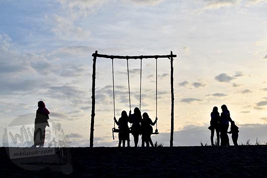 siluet pengunjung wisatawan cewek wanita berjilbab pakai rok berpose di ayunan yang terdapat di Gumuk Pasir Parangkusumo Bantul pada suatu sore senja yang cerah di bulan Agustus 2016