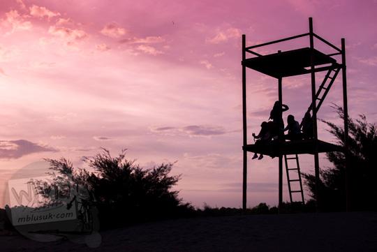 siluet gerombolan sekelompok pengunjung wisatawan cewek wanita berjilbab memadati gardu pandang kayu yang terdapat di Gumuk Pasir Parangkusumo Bantul pada suatu sore senja yang cerah di bulan Agustus 2016