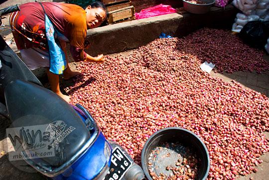 seorang ibu penjual bawang merah di pasar Argosari, Wonosari, Gunungkidul, Yogyakarta sedang menjemur bawang merah di luar pasar agar tidak busuk