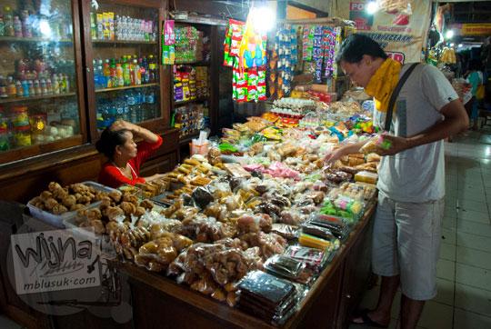 seorang ibu tua penjual jajanan pasar di lantai 2 pasar Argosari di Wonosari, Gunungkidul, Yogyakarta sedang melayani pembeli yang memilih jajanan